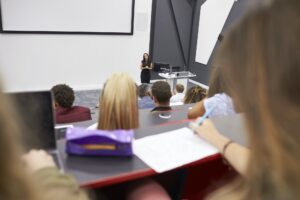 Woman lecturing students in a lecture theatre, student POV